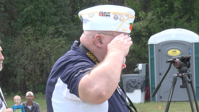 A veteran salutes the American flag as the ceremony begins with The Star-Spangled Banner.