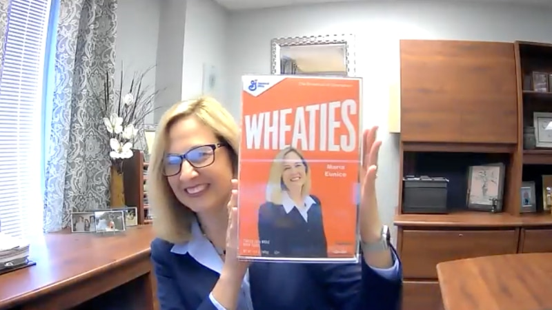 Maria Eunice displaying the Wheaties box gifted to her by General Mills.