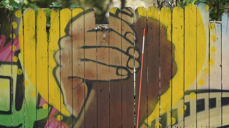 A mural on a fence is displayed at United Fort Worth, a grassroots community organization in...