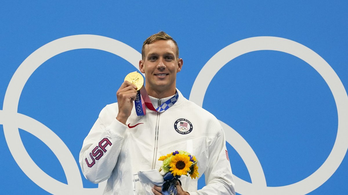 Caeleb Dressel, of United States, poses after winning the gold medal in the men's 100-meter...