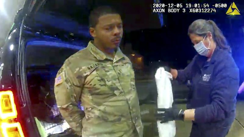 In this image made from Windsor, (Va.) Police video, Caron Nazario is helped by an EMT after he...