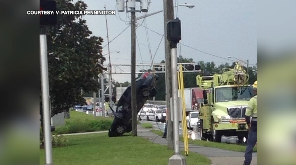 Electric crews remove wrecked car from power lines in Ocala