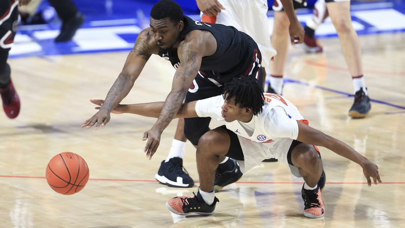South Carolina guard Jermaine Couisnard dives over Florida guard Tyree Appleby for the ball...
