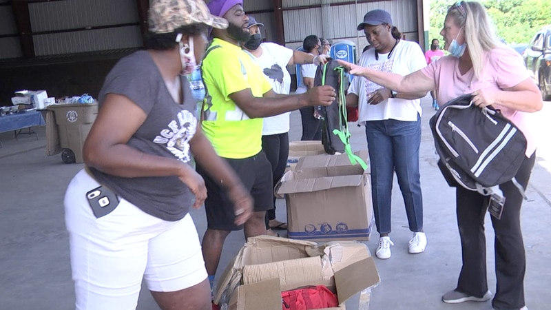 Volunteers handing out thousands of free backpacks.