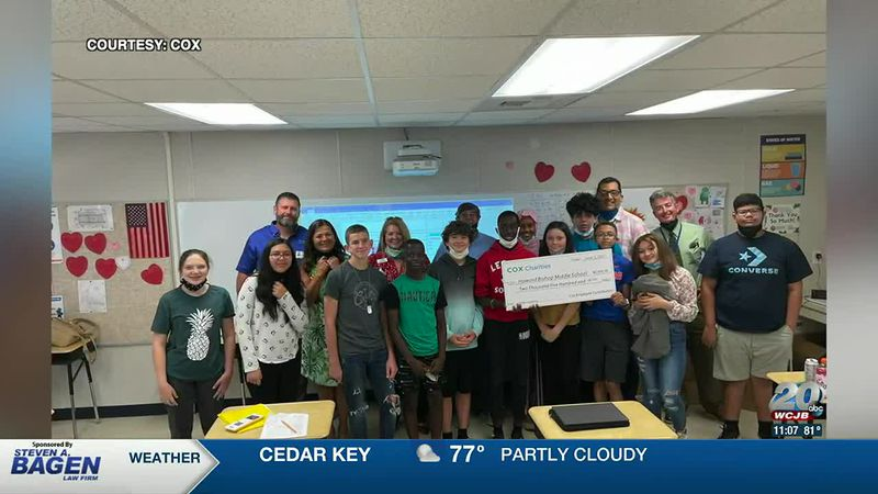 Cox Communications employees give a Gainesville middle school funds to help support STEM skills