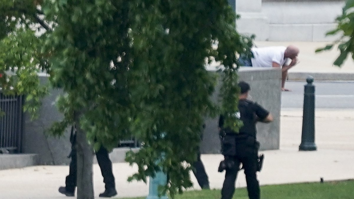 A person is apprehended after being in a pickup truck parked on the sidewalk in front of the...