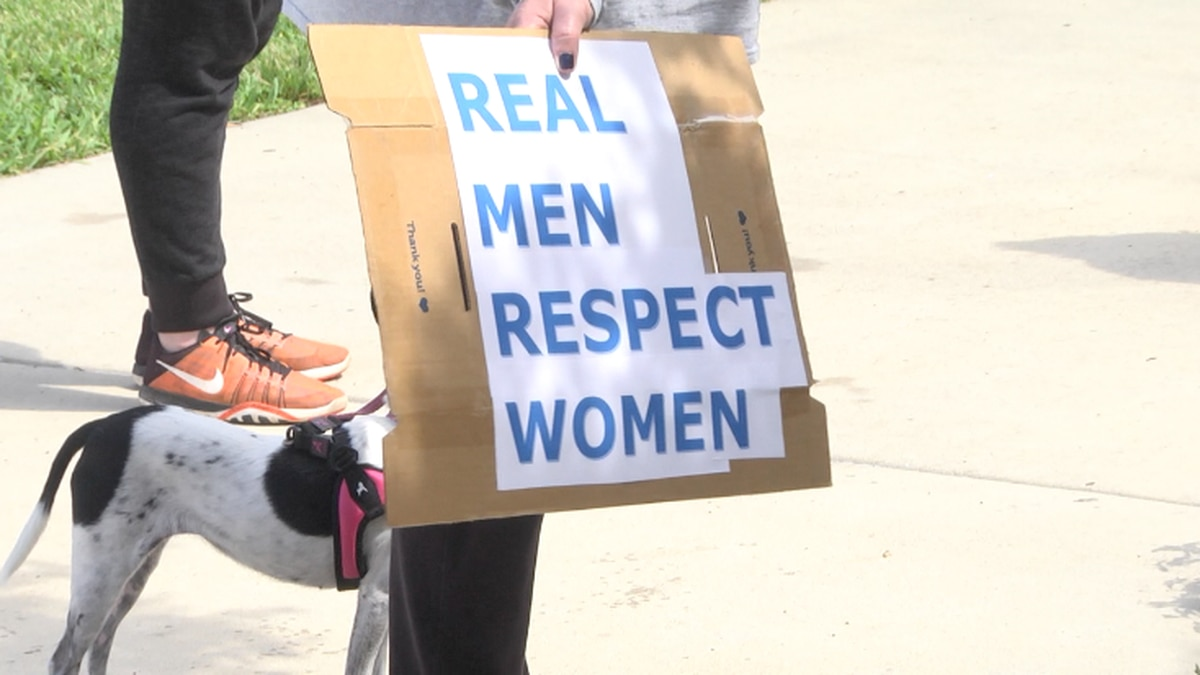 "Woman holds ""Real men respect women"" sign."