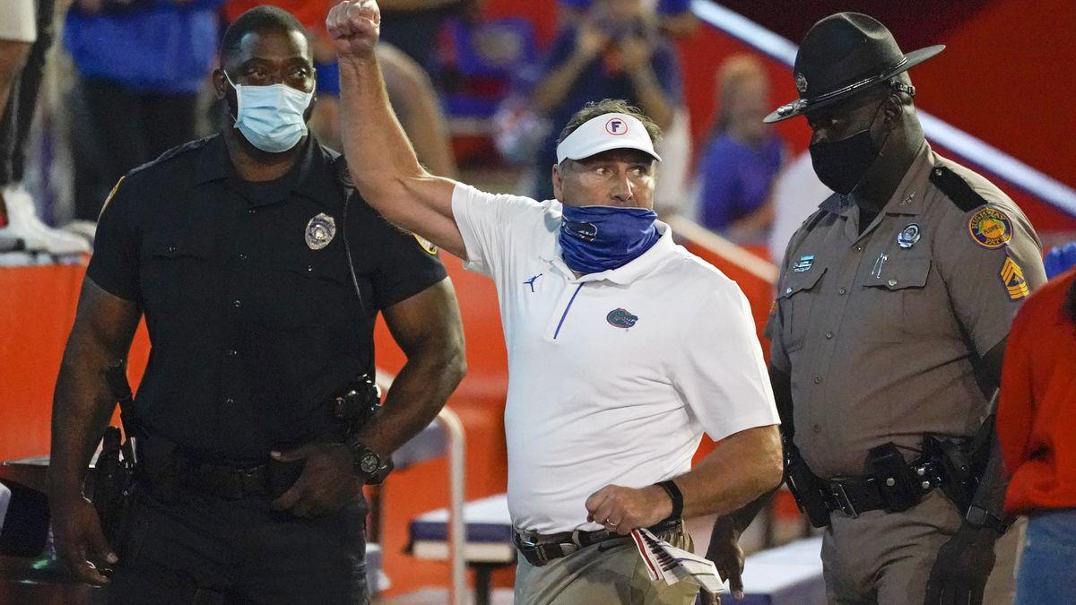 Florida head coach Dan Mullen, center, raises his fist to cheering Florida fans after an...