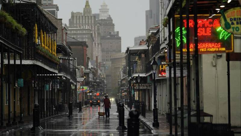 A man pulls a cart down a mostly deserted Bourbon Street in the French Quarter as the early...