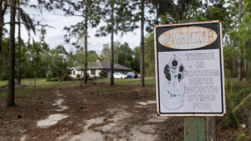 """A sign featuring a pistol barrel pointed at would-be trespassers warns, """"There is Nothing Here..."""