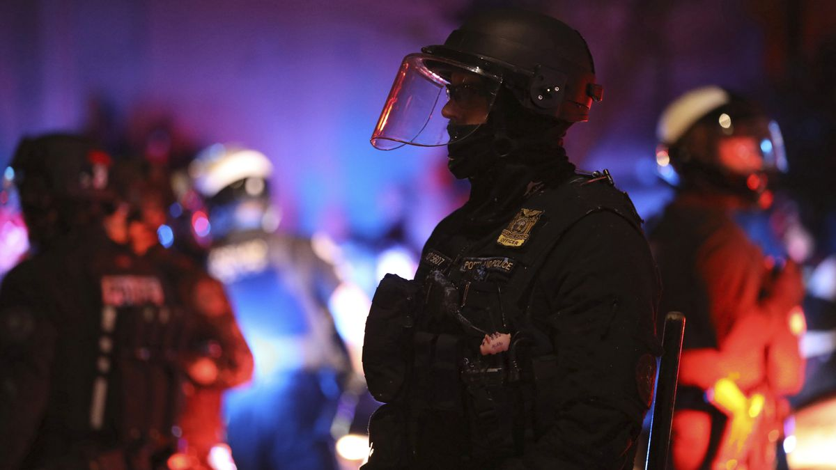 A Portland Police officer watches protesters rallying at the Mark O. Hatfield United States...
