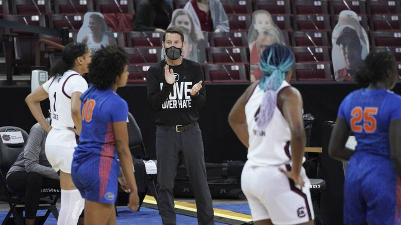Florida coach Cam Newbauer applauds from the sideline during the first half of the team's NCAA...
