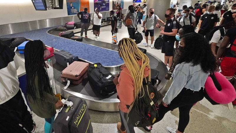 FILE - In this May 28, 2021 file photo, travelers wait for their luggage at a baggage carousel...