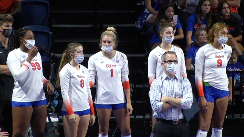 Florida volleyball players look on as their teammates battle Coastal Carolina in a...