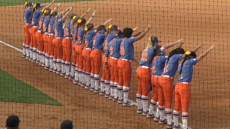 The Gators softball team lines up along the third baseline before play begins to perform their...