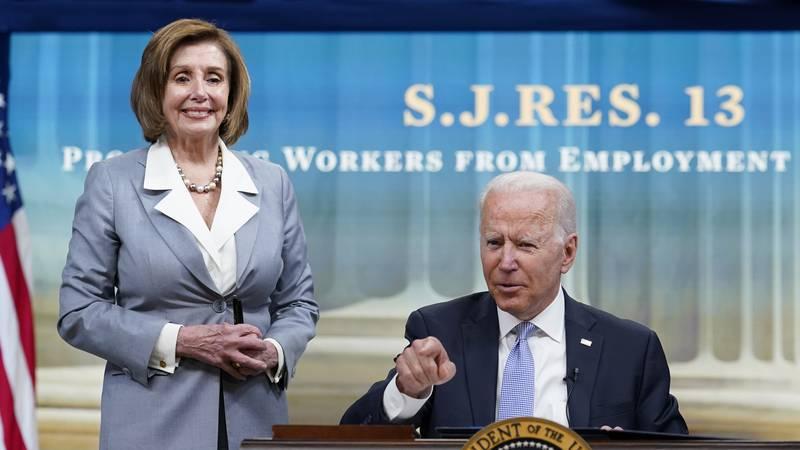President Joe Biden, joined by House Speaker Nancy Pelosi of Calif., talks in-between signing...